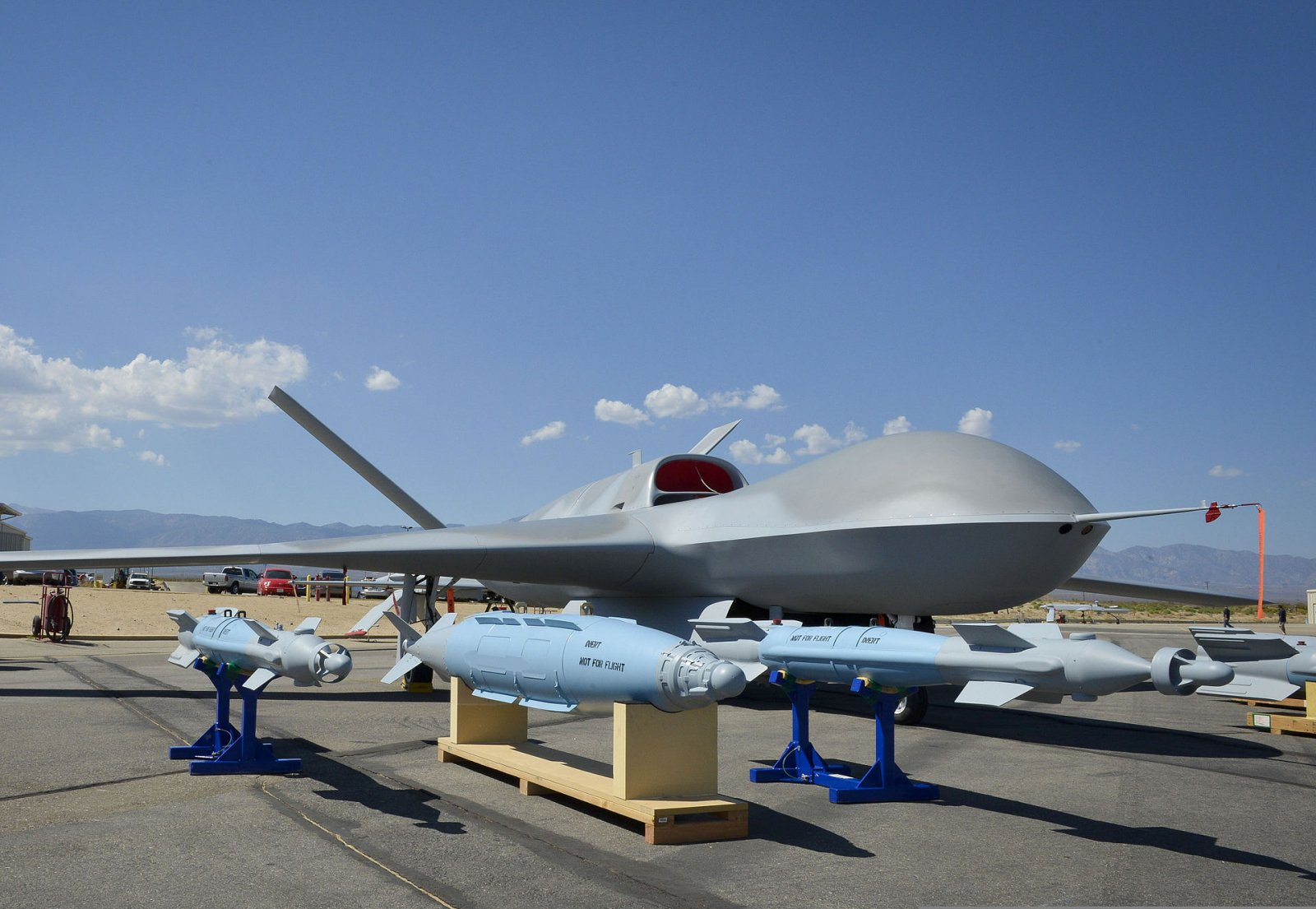 1920px-A_Predator_C_Avenger_unmanned_aircraft_system_and_inert_ordnance_sit_on_display_on_a_ta...jpg