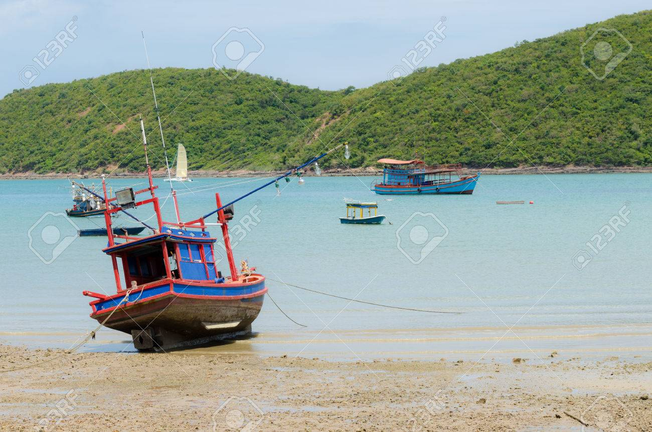 23303652-small-wooden-boat-light-bulbs-for-night-squid-fishing-in-day-light-on-sand-beach-at-t...jpg